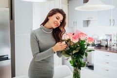 年轻女人发现了玫瑰花束与卡片的在厨房 在花的愉快的女孩读书笔记 红色上升了 库存照片