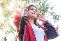 年轻女人听到音乐在公园 免版税库存照片