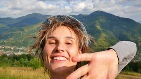 年轻女人告诉某人电话的并且显示在她后的山 影视素材