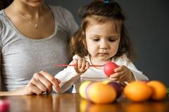 年轻女人和她的女儿在复活节彩蛋一起绘 免版税库存照片