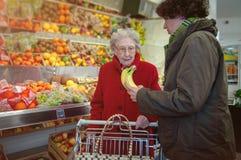 年轻女人和资深妇女在超级市场 库存照片