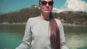 年轻女人在一个春日思考在阳光下,当坐湖的一个木码头,放松本质上时 股票视频