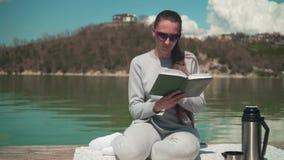 年轻女人在一个春日读一本书在阳光下,坐湖的一个木码头,放松本质上 股票录像
