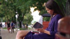 年轻女人在一条长凳的穿戴的随便工作在公园 影视素材