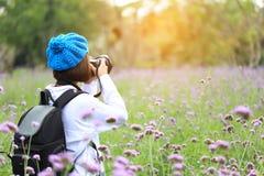 年轻女人在他的手上的拿着DSLR照相机有享用和站立在花背景,旅行生活方式假期的背包的 免版税库存图片