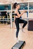 年轻女人在健身俱乐部的做健身锻炼 免版税库存图片