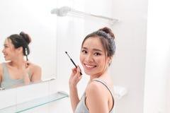年轻女人在卫生间镜子前面在构成站立并且投入 免版税图库摄影