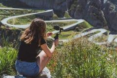 年轻女人在圣gotthard的摄制tremola路使用智能手机和常平架 免版税库存照片