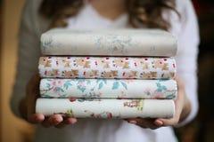 年轻女人在她的手上拿着手被制作的织品学报,堆学报 免版税库存照片