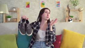 年轻女人在她的手上的拿着鞋子和嗅到令人不快 股票录像