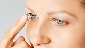 年轻女人在她的眼睛投入隐形 Eyewear、眼力和视觉、眼睛关心和健康、眼科学和视力测定概念, 免版税库存照片