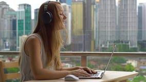 年轻女人在她的膝上型计算机的自由职业者workes在一个阳台有充分市中心的背景的摩天大楼 远程 股票视频