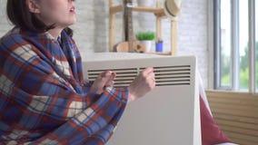 年轻女人在客厅结冰并且在一台电暖气旁边加热自己 影视素材