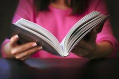 年轻女人在家读一本书 免版税图库摄影