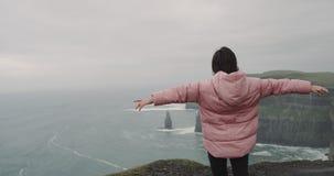 年轻女人在峭壁的上面的令人惊讶的地方到达了站立在岸旁边的她并且敬佩风景  股票录像