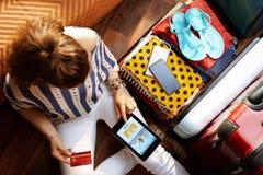 年轻女人在平板电脑的书飞行在开放旅行手提箱附近 免版税库存图片