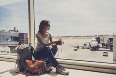 年轻女人在机场,注视着通过窗口飞机和饮用的咖啡、旅行、假期和活跃生活方式conce 免版税库存图片