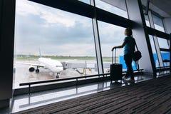 年轻女人在机场,注视着通过窗口飞机 免版税库存照片