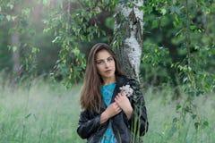 年轻女人在桦树树丛里 免版税库存图片