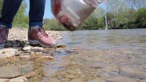 年轻女人在河附近收集垃圾,拔出一个瓶水 环境改善的概念和 股票视频