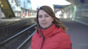 年轻女人在等待她的火车的驻地平台站立 股票视频