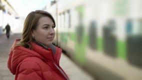 年轻女人在等待她的火车的驻地平台站立 股票录像
