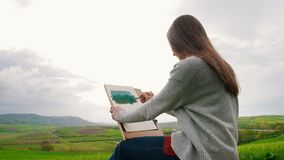 年轻女人在绿色领域和凹道中间坐 在风吹的头发 影视素材