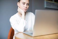 年轻女人在网上学会通过手提电脑的大学生 免版税库存照片