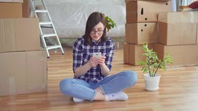 年轻女人在背景箱子使用电话为移动,新的家 股票录像