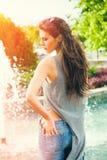 年轻女人在蓝色牛仔裤夏日在城市 库存图片