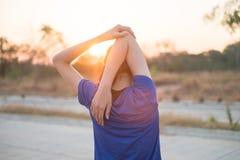 年轻女人在行使前行使在公园 她舒展了她的体检的胳膊有太阳的背景 库存图片