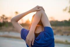 年轻女人在行使前行使在公园 她舒展了她的体检的胳膊有太阳的背景 免版税库存照片