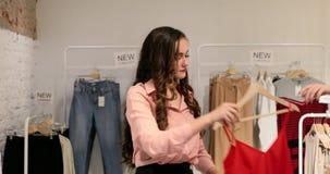 年轻女人在衣裳商店试穿衣裳 股票录像