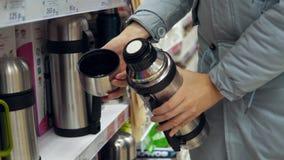 年轻女人在超级市场选择钢热水瓶 股票视频
