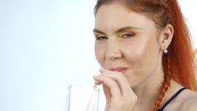 年轻女人在轻的背景的享用和饮料橙汁过去 慢的行动 影视素材