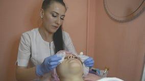 年轻女人在长沙发说谎在专业美容师和皮肤病学家诊所 女性医生洗涤皮肤  股票录像