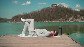 年轻女人在阳光下,在湖的一个木码头说谎在一个春日,放松本质上 股票视频