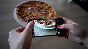 年轻女人在餐馆做照片与手机照相机的食物 妇女做照片比萨 影视素材