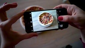 年轻女人在餐馆做照片与手机照相机的食物 影视素材