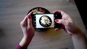 年轻女人在餐馆做照片与手机照相机的食物 妇女做照片沙拉 股票录像
