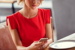 年轻女人在餐馆坐的聊天的日期与智能手机严肃的特写镜头的男朋友 免版税库存图片