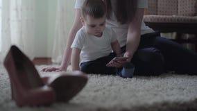 年轻女人坐与一个小男婴的地板并且显示他动画片在手机 股票视频