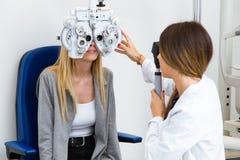 年轻女人坐与美好的眼镜师身分的椅子,当做在眼科学诊所时的眼睛测试 免版税库存照片