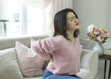 年轻女人坐在家遭受腰疼的长沙发 库存图片