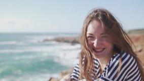 年轻女人坐在岩石的峭壁和神色在海 股票视频