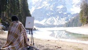 年轻女人坐在白云岩的格子花呢披肩盖的椅子 画在自然的一张绘画 影视素材