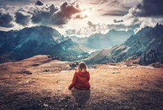 年轻女人坐小山反对山 免版税库存照片