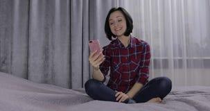 年轻女人坐床和享用有视频聊天使用智能手机 股票录像