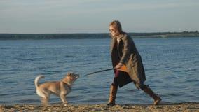 年轻女人奔跑,与一条棕色狗拉布拉多的戏剧在河的河岸的海滩 ?? 影视素材