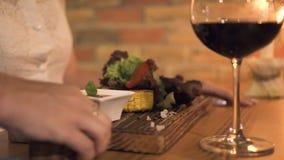 年轻女人定货在典雅的餐馆烤了肉 得到晚餐的女孩肉格栅在烤肉店 夜间 影视素材